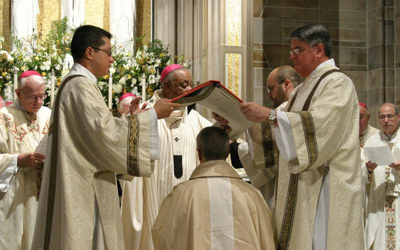 DEACONS HOLD BOOK OF GOSPELS OVER HEAD OF ATLANTA AUXILIARY DURING EPISCOPAL ORDINATION